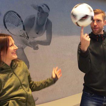 Miriam Willems lässt einen Fußball auf dem Finger von Per Mertesacker drehen