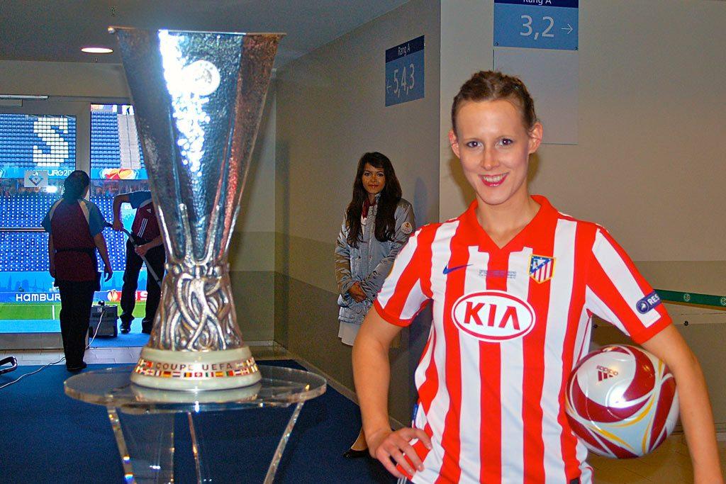Fußball-Akrobatin Miriam Willems neben dem Pokal der UEFA Europa League